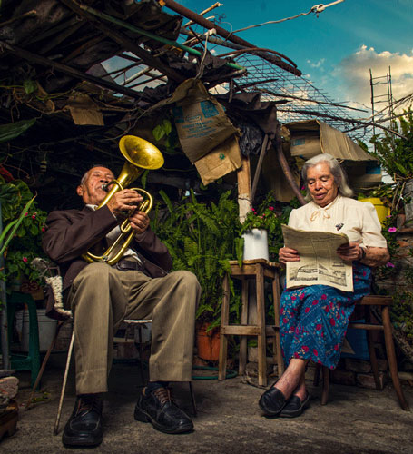 Couple in their garden, reading and making music, Mexico